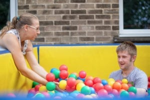 A service user enjoys time in the colourful ball pit