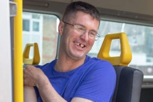 A service user sitting in the mini bus and smiling