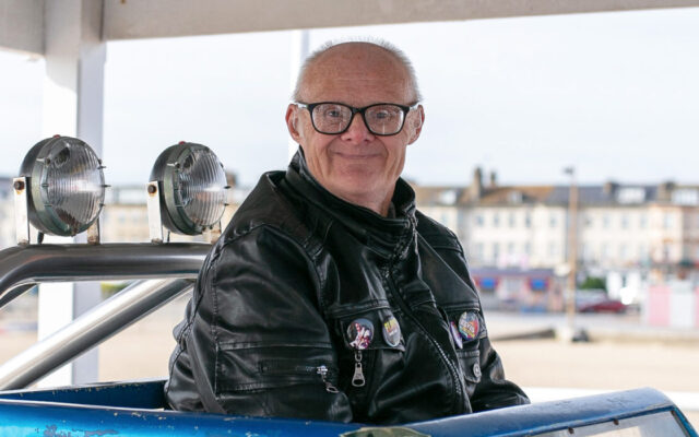 A service user enjoying one of the rides on a day out to the seaside