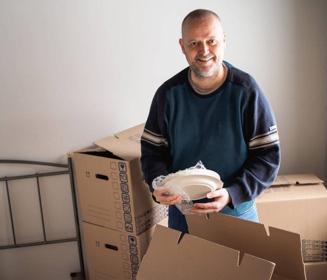 Robert moves into his new home and smiles as he unpacks his things